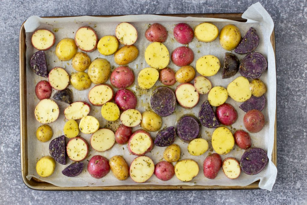 overhead view of parchment lined sheet pan with uncooked sliced red yellow and purple potatoes with oil herb coating. slate gray background