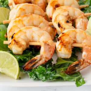 platter of chili-lime shrimp on skewers on bed of greens with lime slices