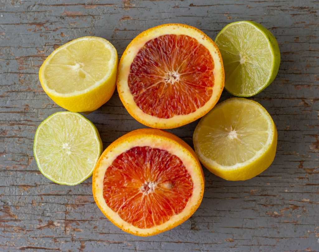 overhead view of halved lemon, blood orange and lime on weathered wood board