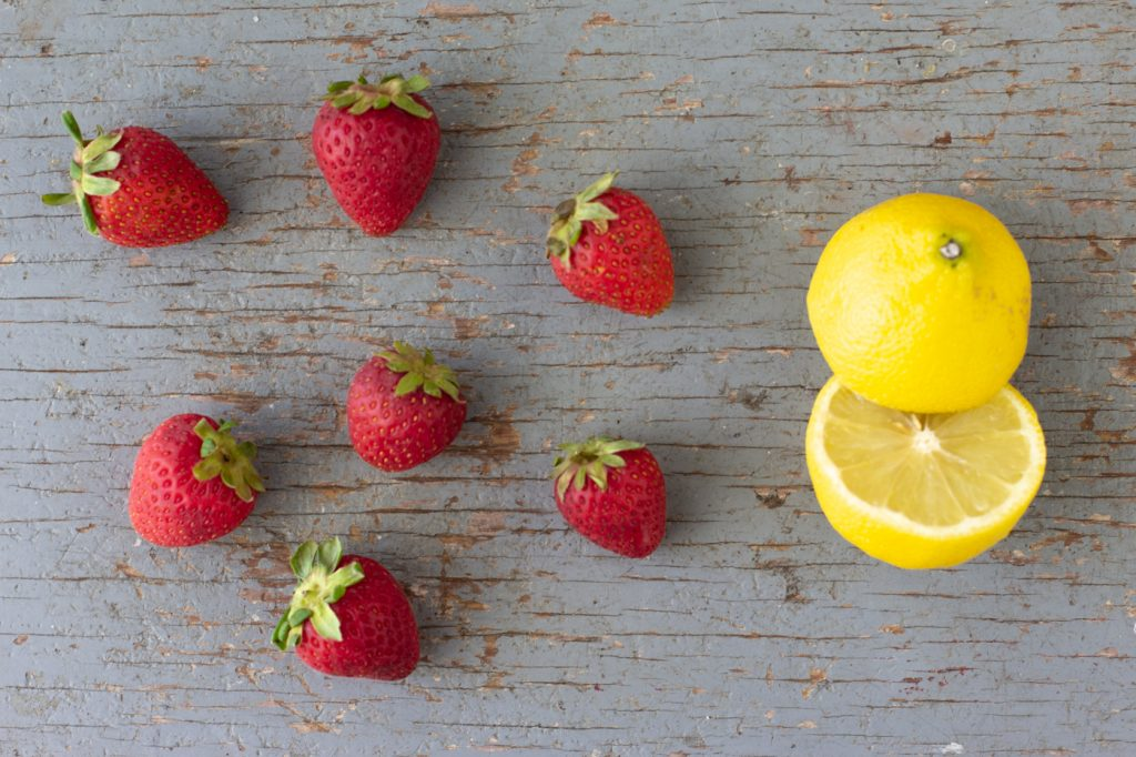 overhead view of strawberries and halved lemon on weathered blue wood board