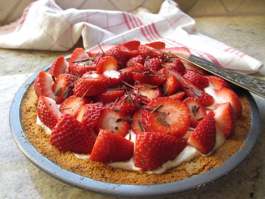 Close up of gluten-free fresh strawberry pie in graham cracker crust with shaved chocolate topping. White and red plaid napkin in background. Pie server on right.