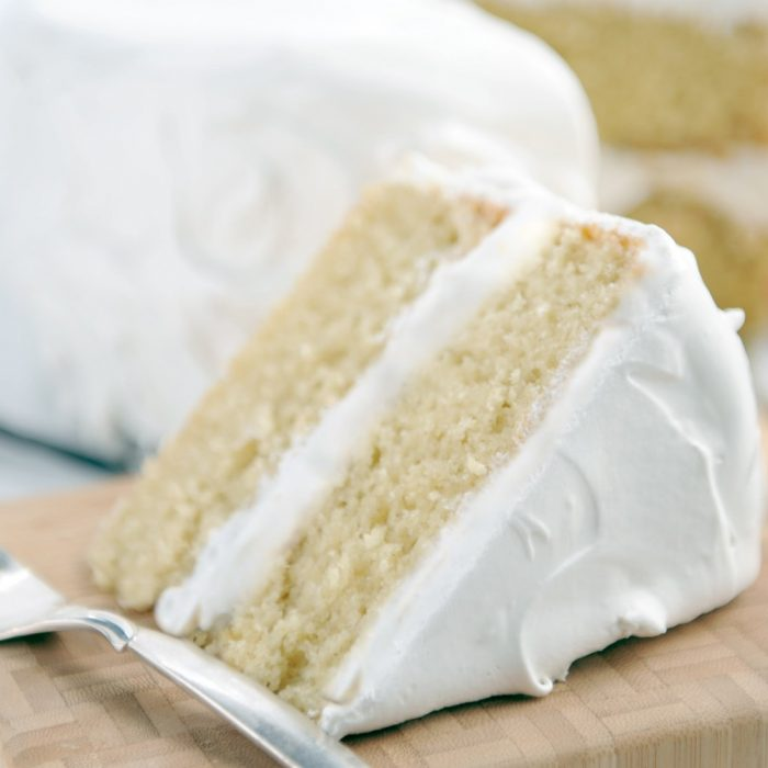 slice of gluten-free vanilla layer cake with white frosting, whole cake in background