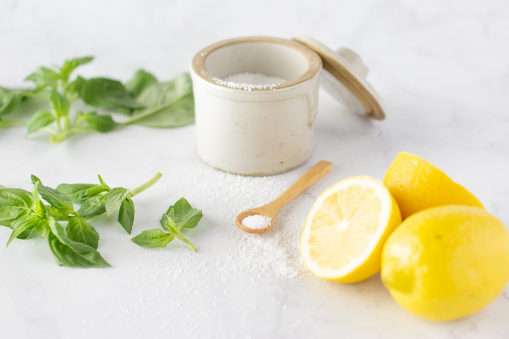 crock with coarse salt, small wood spoon with salt, sprigs of fresh basil and lemons  for lemon basil dressing on white marble background