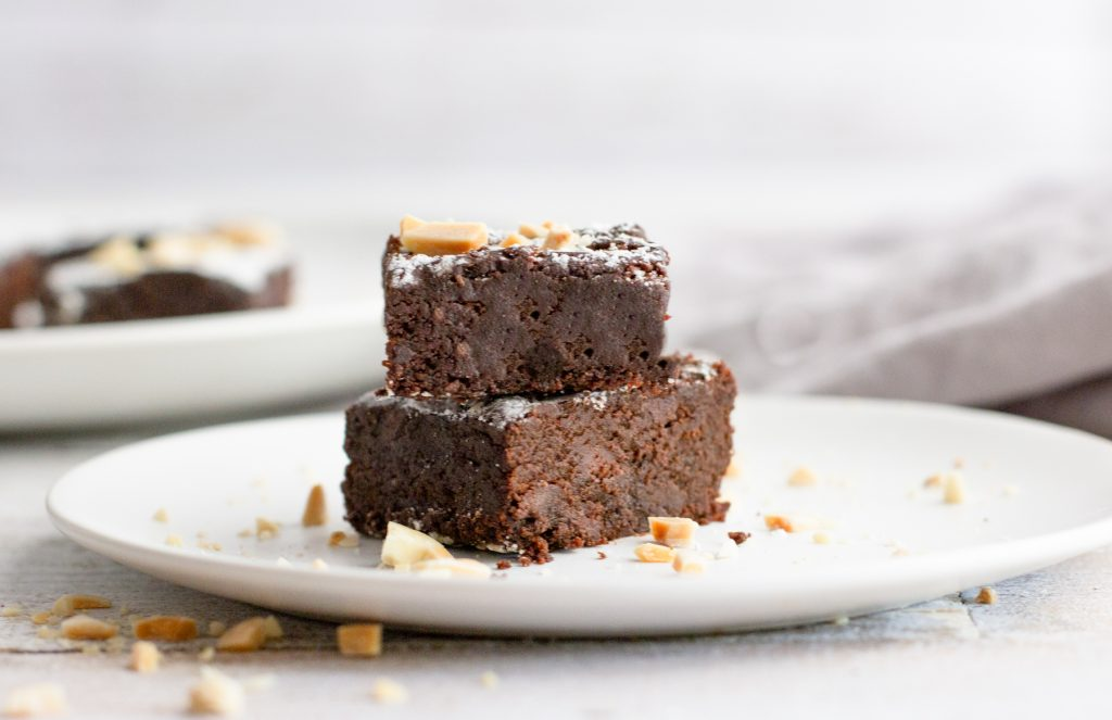 2 GLUTEN FREE FUDGE BROWNIES STACKED ON WHITE PLATE with powdered sugar and slivered almonds