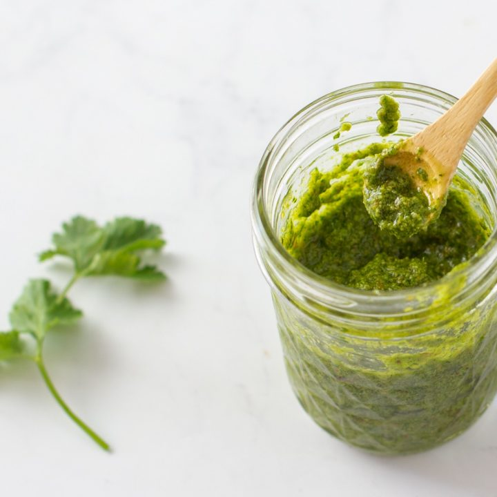 overhead view of jar of cilantro lemon pesto with wood spoon dipping in. cilantro leaves on left. white marble background
