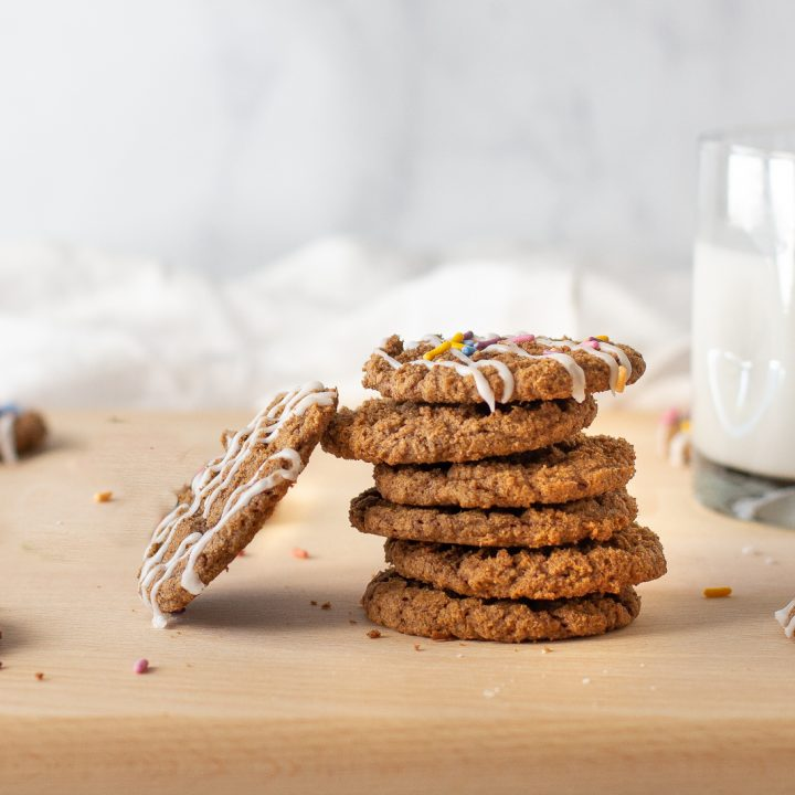 stack of cinnamon mesquite cookies on wood board with milk glass on right. white background