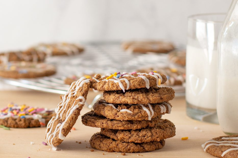 stack of cinnamon mesquite cookies with icing and rainbow sprinkles. Milk glass and bottle on right. Cookies on wire rack in background.