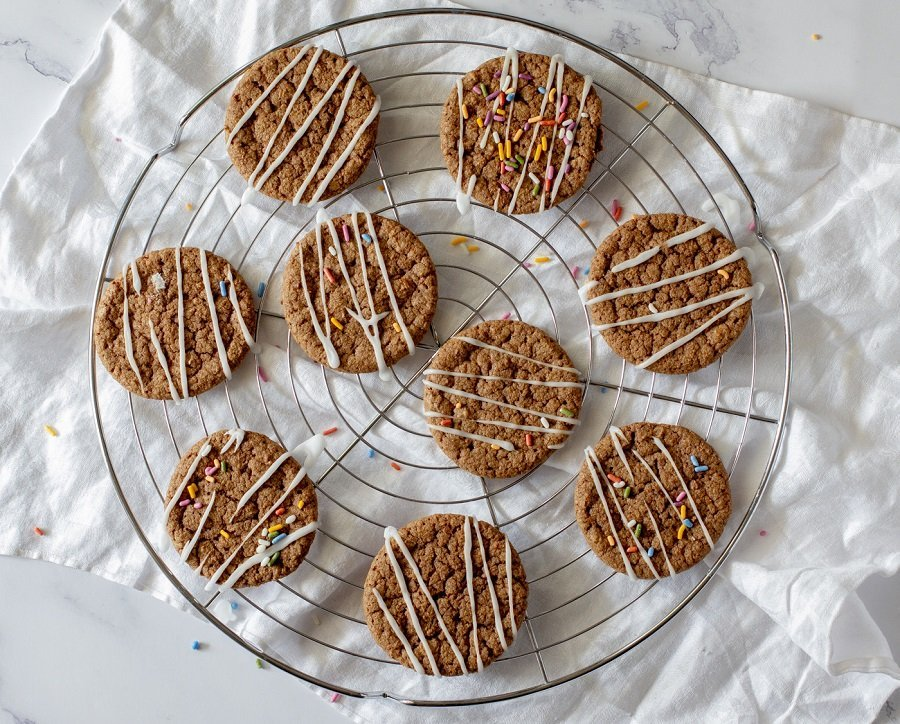 overhead view of gluten free cinnamon mesquite cookies on round wire rack with white napkin underneath