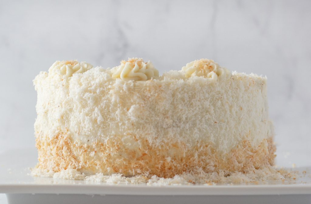 close up of 2 layer gluten-free coconut cake with vanilla buttercream forsting coated in shredded coconut. white marble background