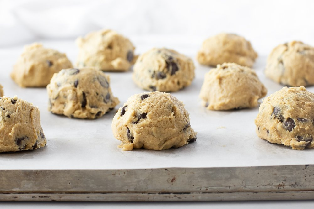 close up of gluten free chocolate chip cookie dough on parchment