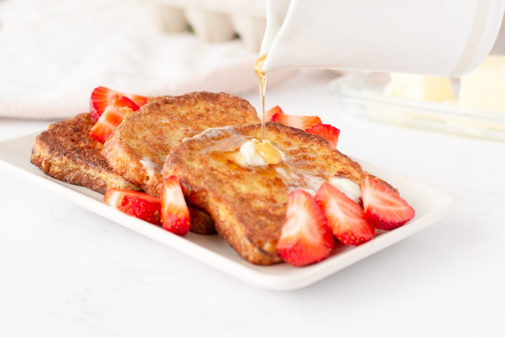 3 slices crispy french toast on square white plate with butter and sliced strawberries. White pitcher above pouring syrup. White background
