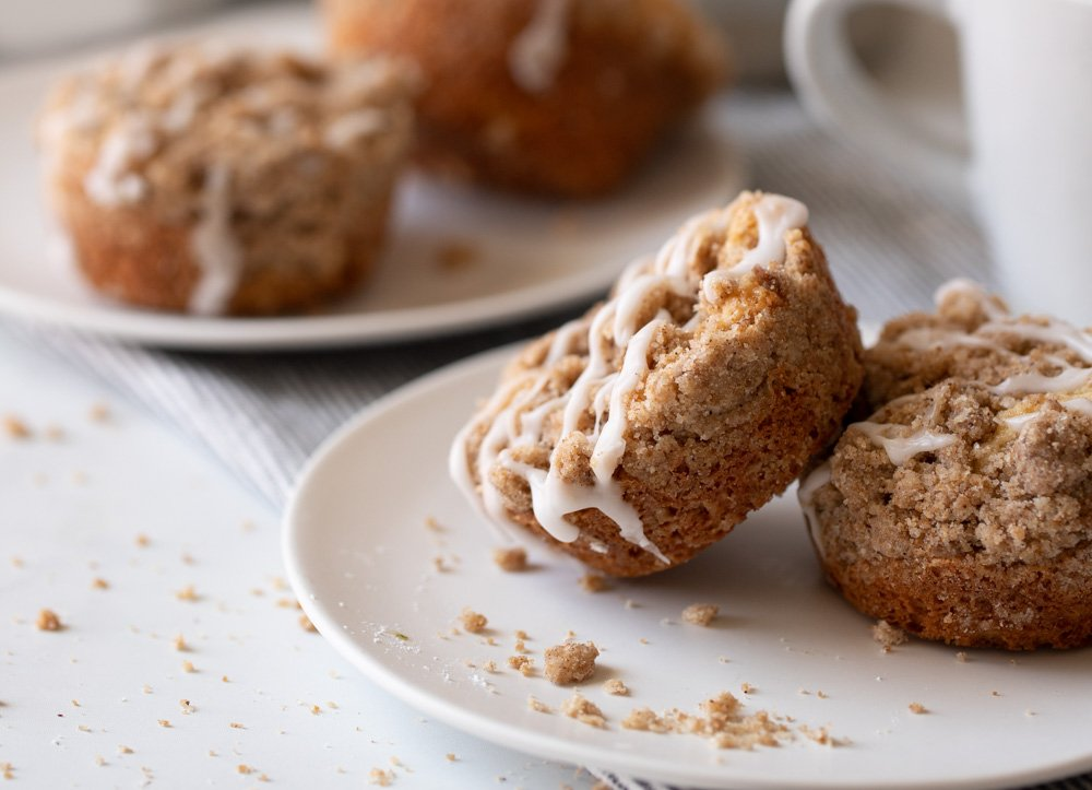 2 gluten free coffee cake muffins on white plate with white coffee mug on right and plate with muffins in background.