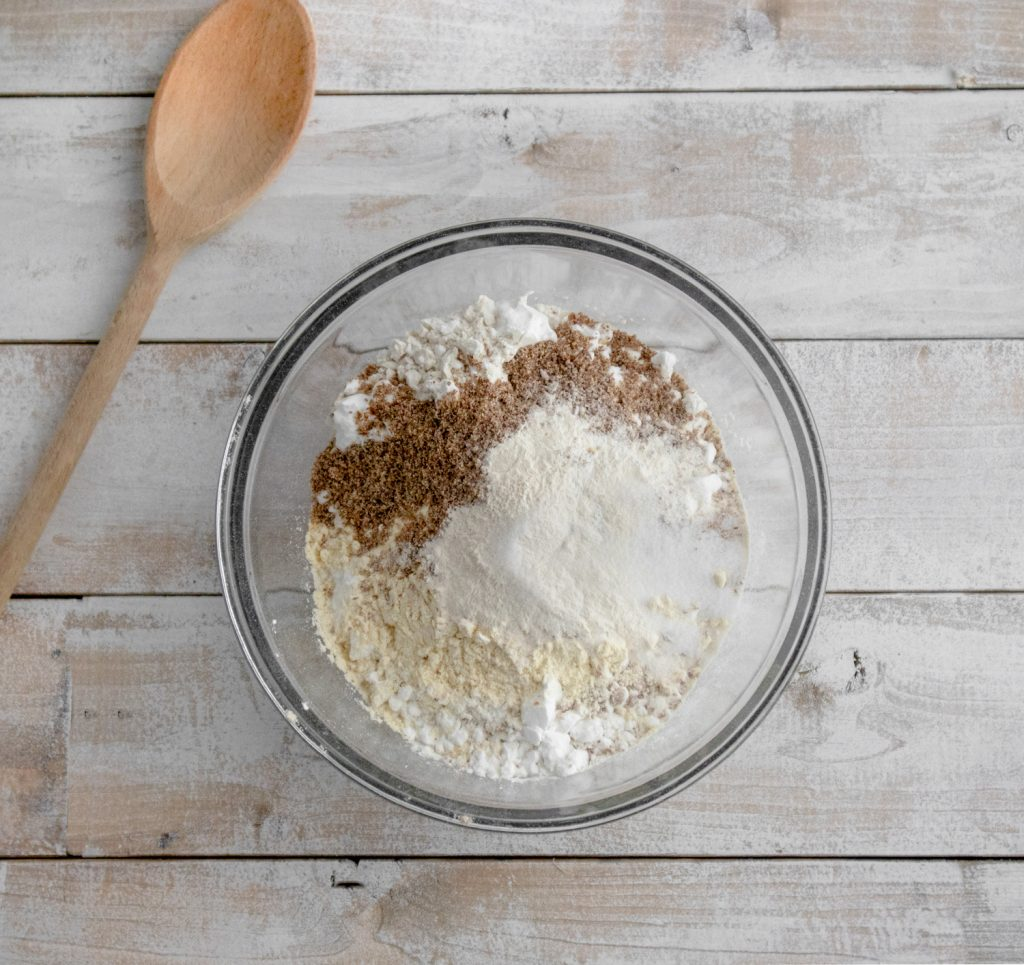 overhead shot of clear glass bowl with gluten-free flours on weathered wood board background and wood spoon on left