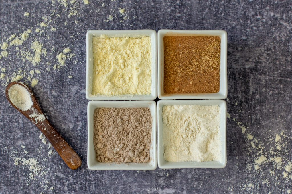 overhead view of square white bowls  with gluten-free flours. small wood spoon on left on gray stone background