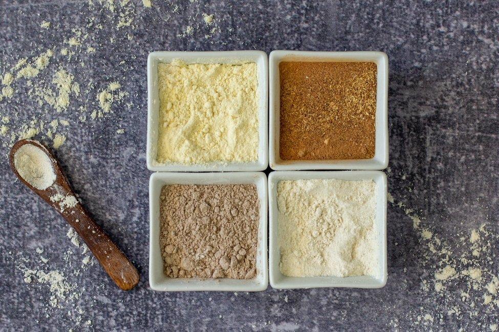 small square white bowls with gluten-free flours - teff flour, mesquite flour, millet flour and sorghum flour