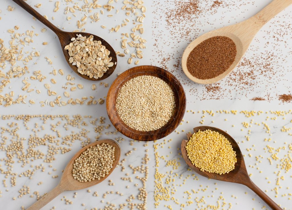 overhead view of gluten-free grains on white background. wood bowl of quinoa in center with wood spoons of millet grain, sorghum grain, teff grain and rolled oats