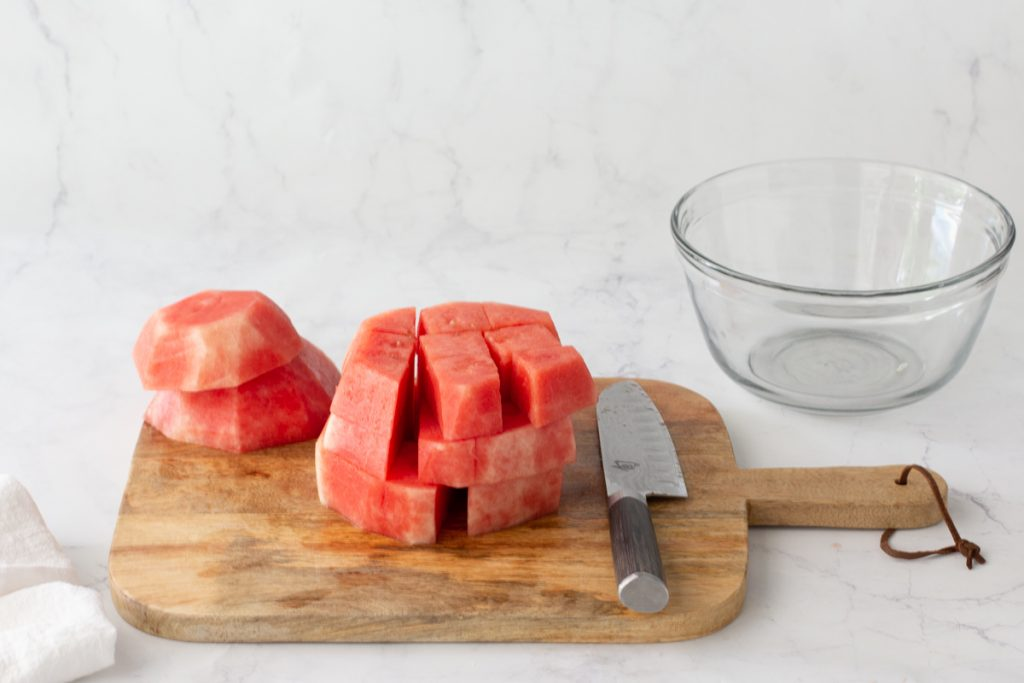 ound slabs of watermelon with rind cut off, cut into cubes on wood cutting board. Knife in front, clear glass bowl in back