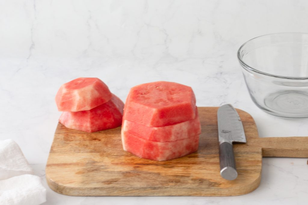 stack of round slabs of watermelon with rind cut off on wood cutting board. Knife in front, clear glass bowl in back