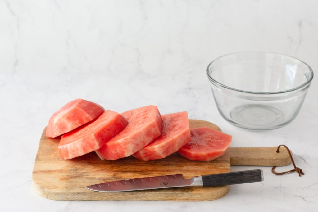 round slabs of watermelon with rind cut off on wood cutting board. Knife in front, clear glass bowl in back