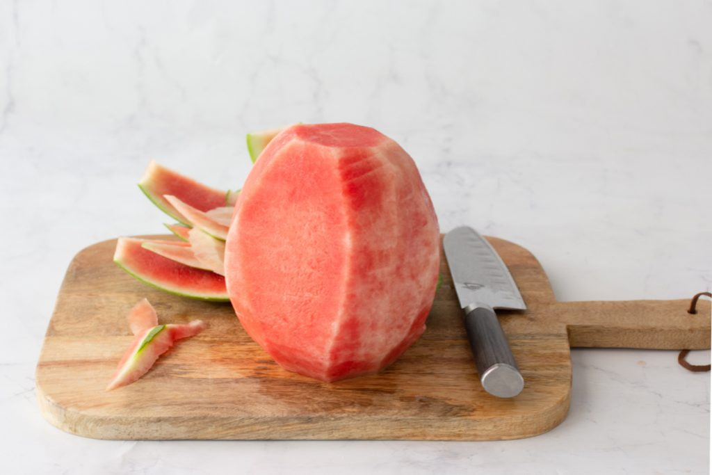 whole watermelon with rind cut off on wood cutting board with white marble background
