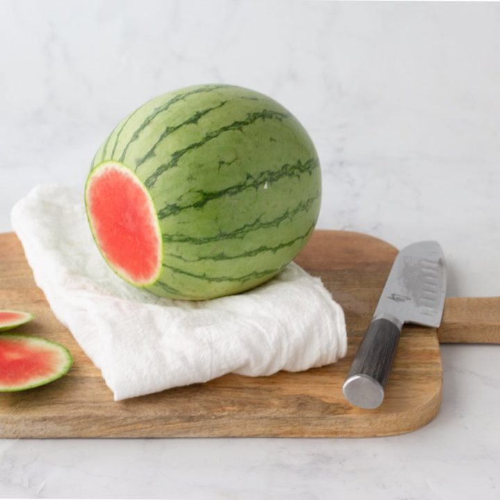 whole watermelon with ends trimmed off with a white towel underneath on wood cutting board with knife on right