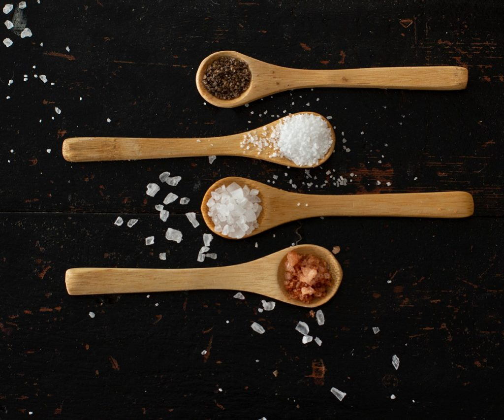 overhead view of small wood spoons with different types of salt on black wood background