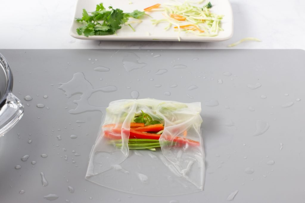 rice paper wrap with veggies. top of wrapper folded down and sides folded over
