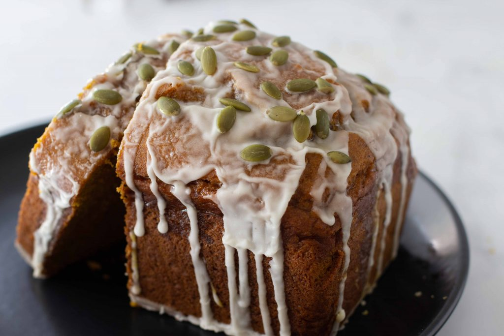 half loaf of gluten-free pumpkin bread with rim icing and pumpkin seeds on black plate with white background