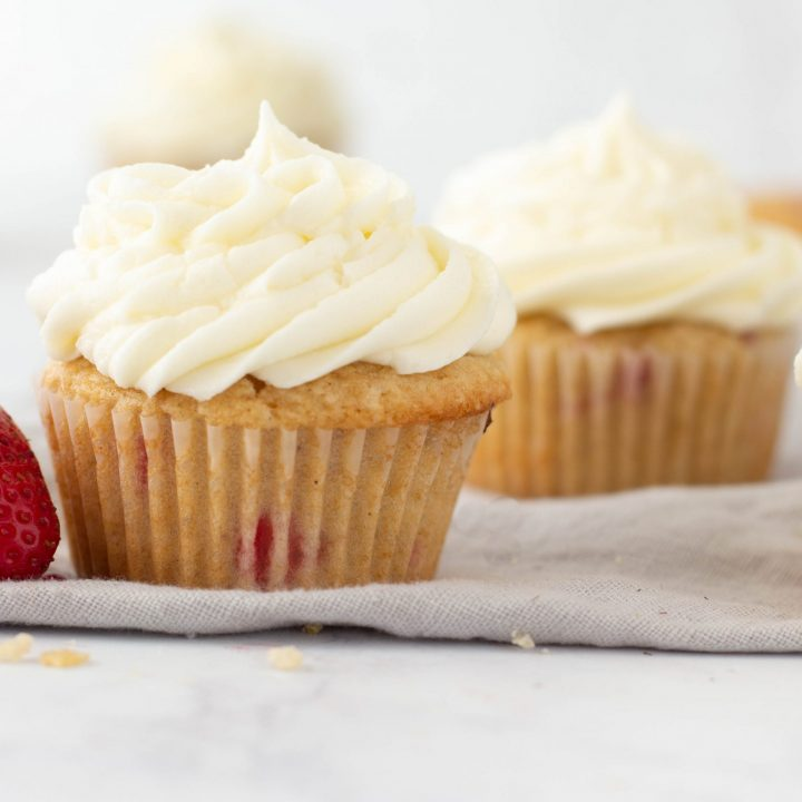 close up of gluten free strawberry cupcakes with vanilla buttercream frosting, strawberry on left, white background