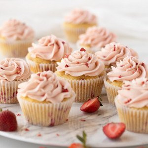 gluten free strawberry cupcakes with pink icing on white marble platter. Cut strawberries scattered. White Background