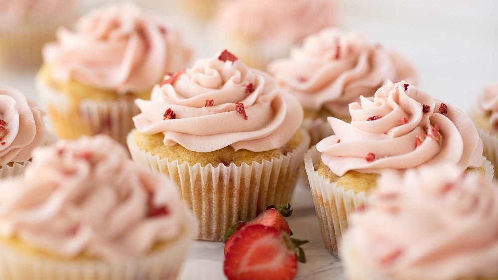 Close up of guten-free strawberry cupcakes with pink frosting, topped with chopped freeze dried strawberries on white marble plate. Cut strawberries in front.