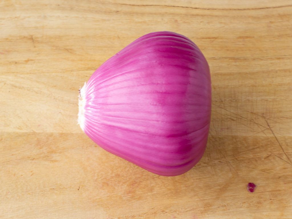 whole red onion on cutting board