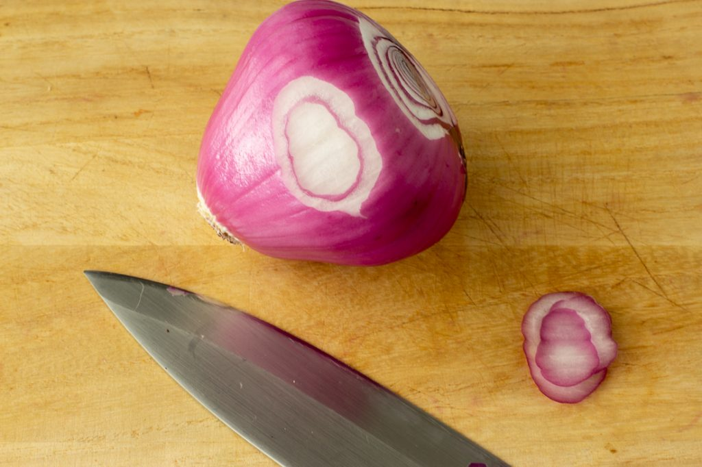 red onion with slice cut off on wood cutting board