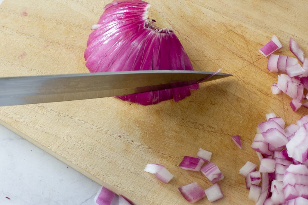 onion on cutting board being diced