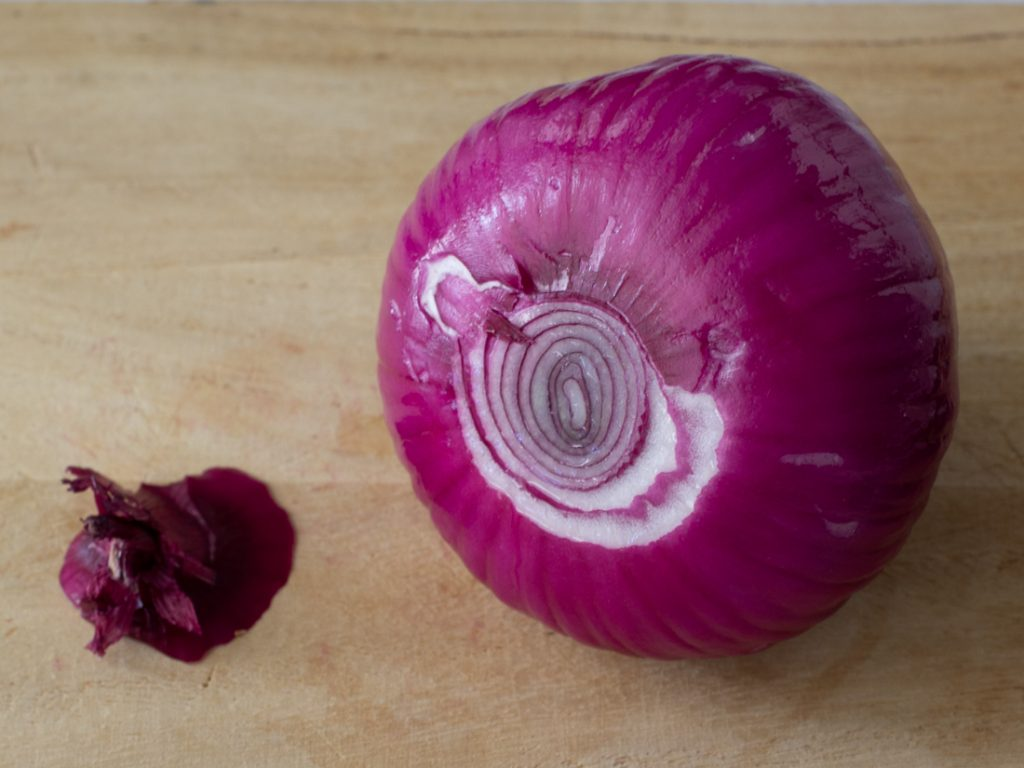 red onion on cutting board with stem end trimmed off