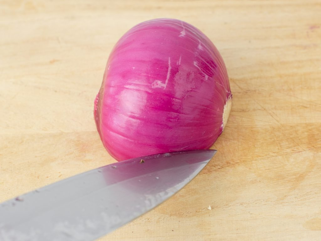 half red onion on cutting board with knife cutting into it
