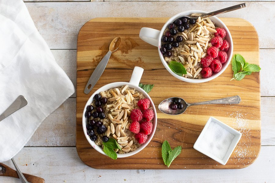overhead view of 2 quinoa breakfast bowls in white mugs topped with raspberries, blueberries and almonds and mint leaves on wood board. spoons and white bowls and white napkin on left