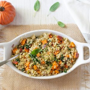 overhead view of white oval serving dish with quinoa yam stuffing on burlap mat on white background. small pumpkins in upper left and white napkin on right