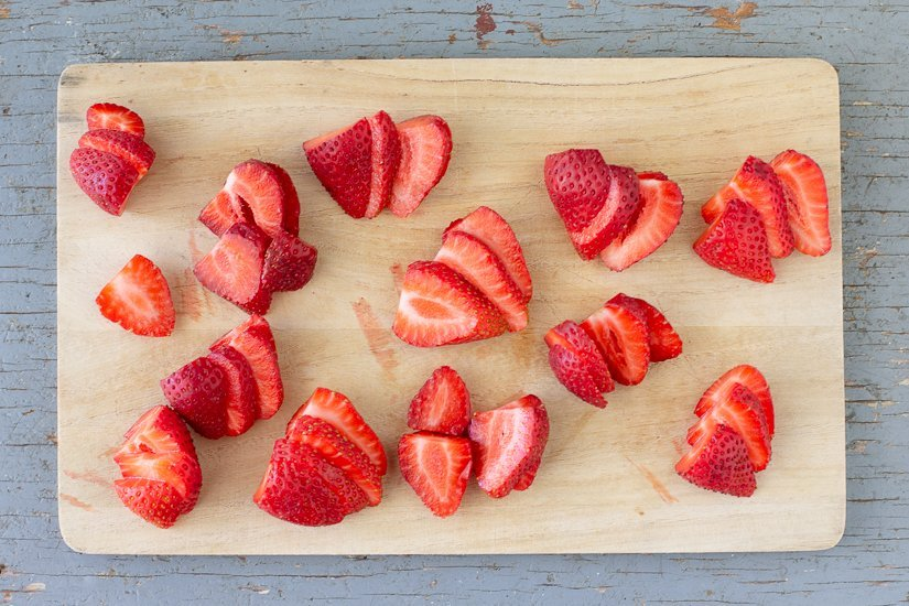 overhead view of sliced strawberries on cutting board with blue weathered wood background