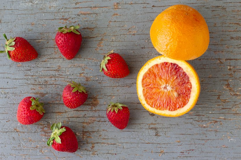 overhead view of whole strawberries and halved orange on blue painted wood background