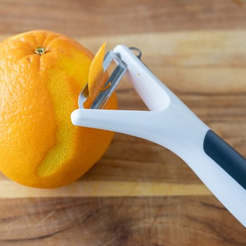 close up of vegetable peeler shaving zest off an orange on a wood cutting board