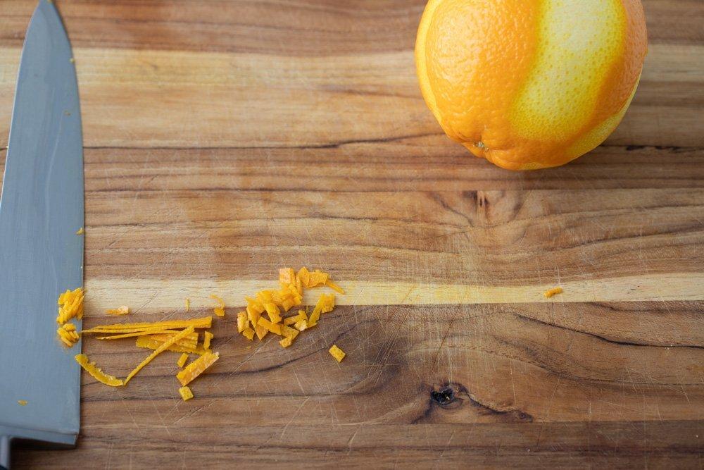 orange zest partially minced on wood cutting board