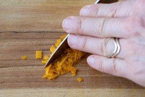 hand on back of knife mincing orange zest on wood board