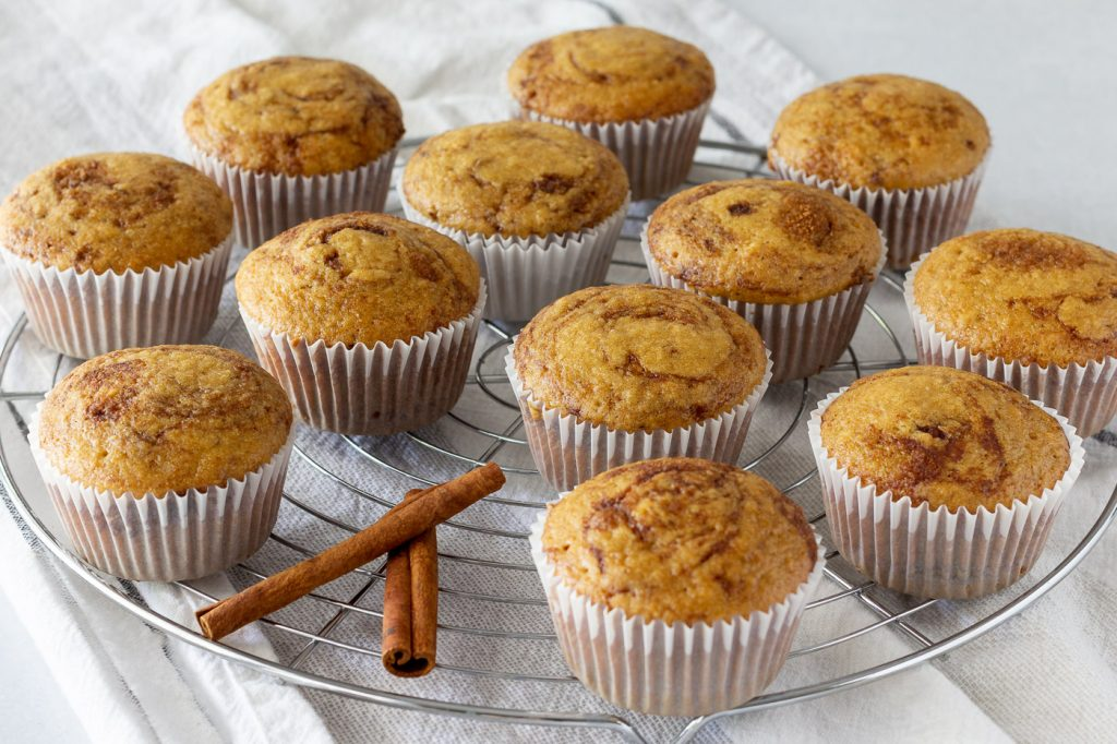 gluten free dairy free muffins with cinnamon and apple on round wire rack with cinnamon sticks