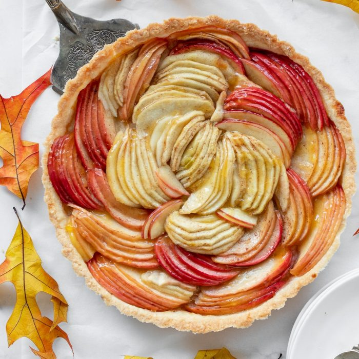 overhead view of gluten free apple tart surrounded by autumn leaves. Pie server and stack of plates with forks and napkin in corners