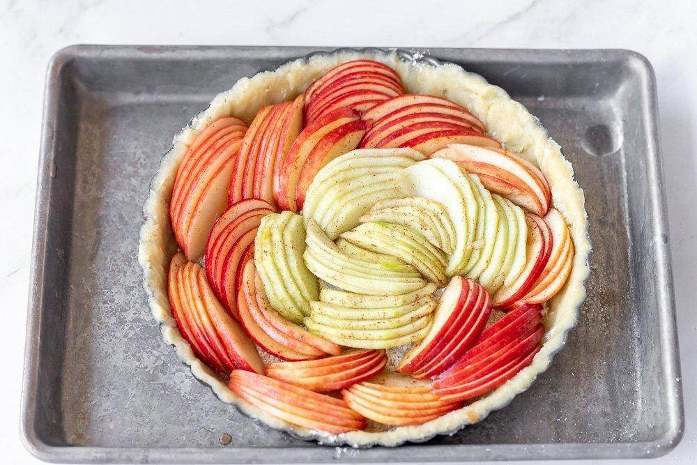 overhead view of unbaked apple tart on sheet pan