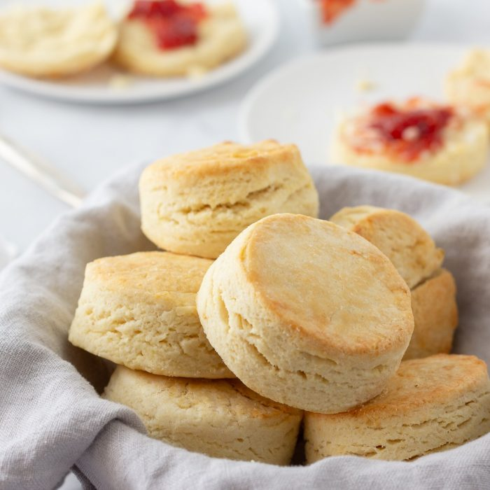 gluten free biscuits in bowl with gray napkin. Biscuits with jam on white plates in background