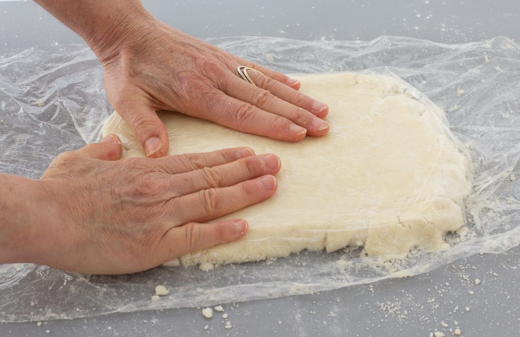gluten-free biscuit dough on counter covered in plastic with hands flattening dough.