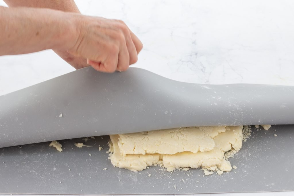 dough on silicone mat. Dough being folded in half top to bottom