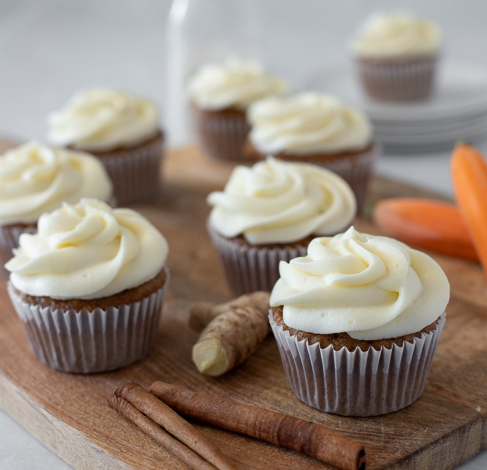 gluten free carrot cake cupcakes with cream cheese frosting on wood board with fresh ginger, cinnamon sticks and whole carrots. Milk bottle and stack of plates in background